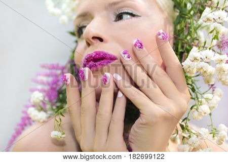 Beautiful woman with design of summer pink flower Astilbe on the lips and on the fingers.The nail design.White pink manicure and makeup.