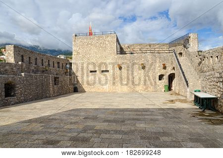 HERCEG NOVI MONTENEGRO - SEPTEMBER 25 2015: Unknown tourist sits on ramparts of Sea Fortress (Forte Mare) in Old Town Herceg Novi Montenegro