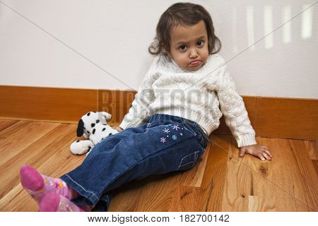 Mixed race girl sitting on floor pouting