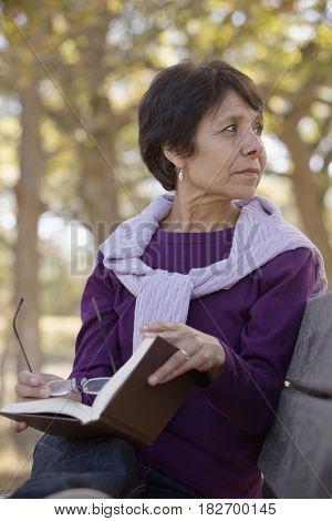Hispanic woman reading book in park