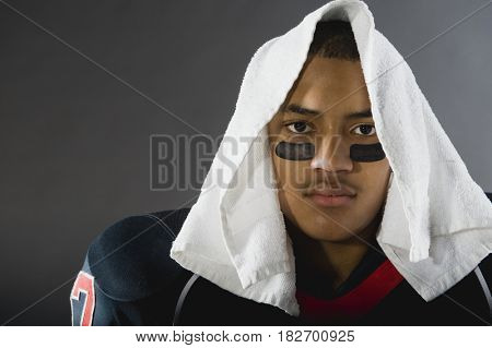 Mixed race football player with towel on head
