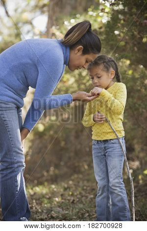 Hispanic woman exploring park with daughter