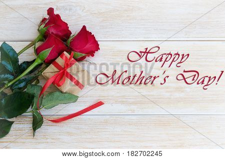 Bouquet of red roses flowers and gift box with ribbon and bow on wooden background. Concept for Happy mother´s day greeting card.