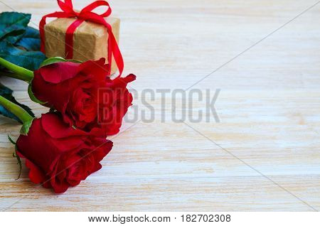 Three red roses and gift box for your Mother in Mothers Day. Beautiful flower bouquet and gift on wooden background with copy space for greeting message.