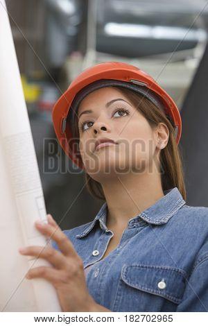 Hispanic woman in hard-hat holding blueprint