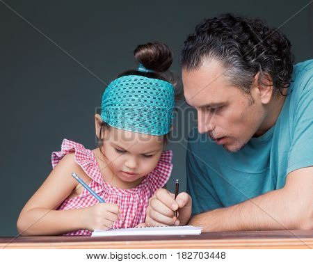 Father schooling his young daughter. Home schooling