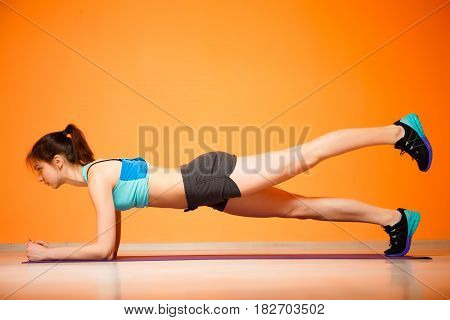 Young woman doing exercises on rug in gym