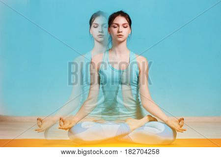 Young athlete in lotus pose on rug, effect of bifurcation