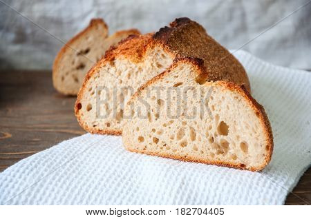 Close Up Of Freshly Baked Sourdough Whole Wheat Flour Bread Loaf On A White Napkin. Copy Space.