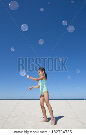 Eurasian girl playing with bubbles on beach
