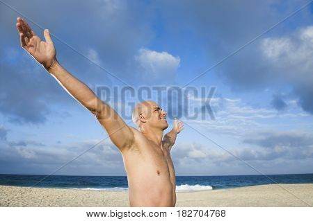 Mixed race man standing with arms outstretched on beach