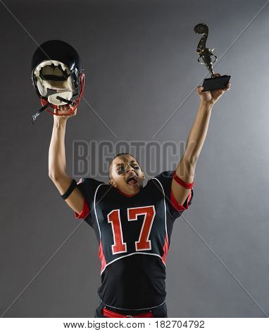 Mixed race football player holding helmet and trophy overhead