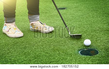 Kids Feet With Golf Club And Ball Going To The Hole