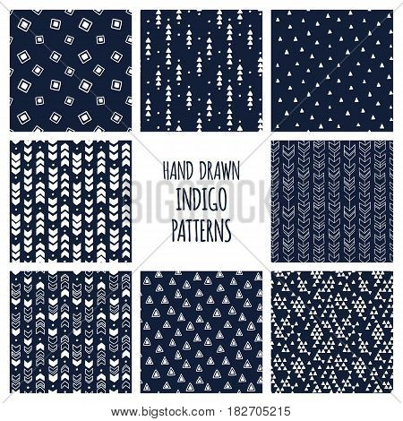 Set of hand drawn indigo blue patterns. Seamless triblal backgrounds with triangles and arrows. Vector illustration.