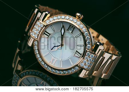 Elegant golden with diamond men's watch against dark background