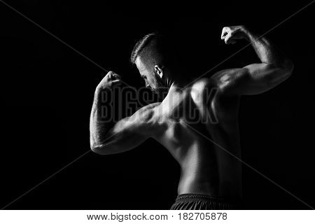 The colorless image of back of torso of attractive male body builder on black studio background.