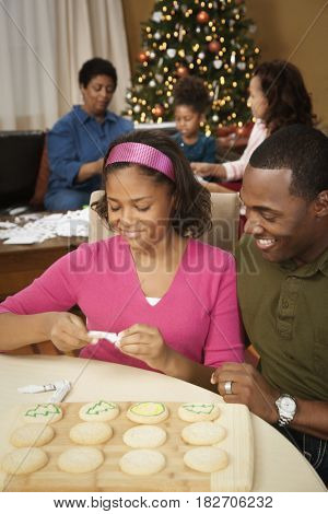 Father and daughter decorating Christmas cookies