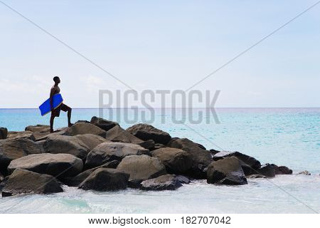 African man holding body board on rocks in ocean