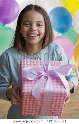 Hispanic girl holding birthday gift and smiling