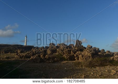 Gorgeous look at a pile of rugged lava rocks with the lighthouse in the background.