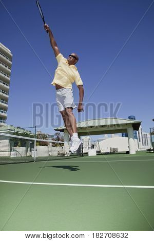 African tennis player jumping with racket