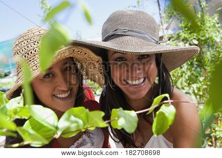 Smiling Hispanic women wearing hats