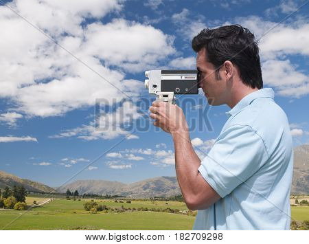 Mixed race man using retro video camera
