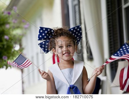 Mixed race girl holding American flags