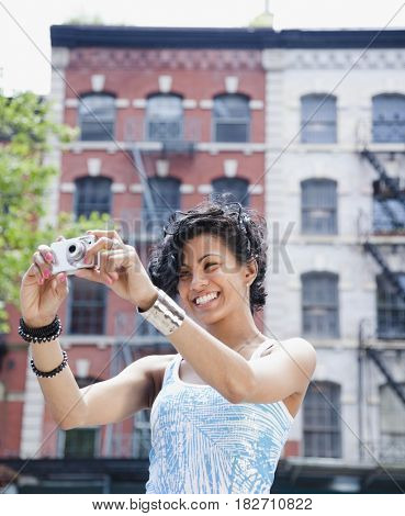 Mixed race woman taking photograph with digital camera
