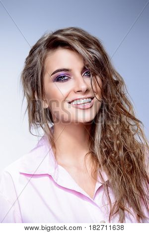 Close-up portrait of a smiling young woman with shaggy hair. Beauty, fashion. Make-up. Hairstyle.