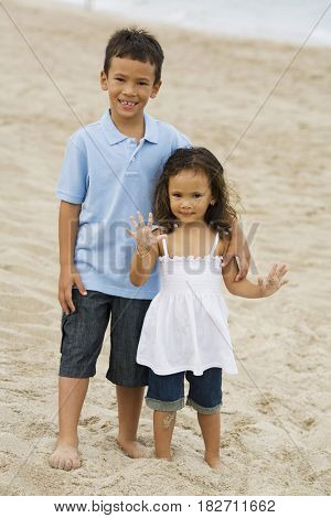 Mixed race brother and sister on beach