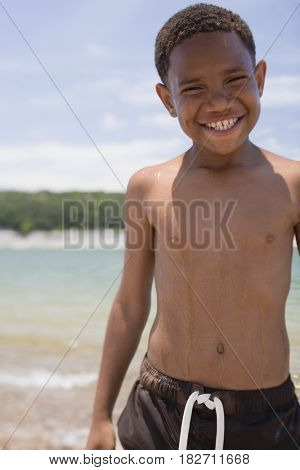 African boy wearing swim trunks on beach