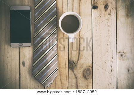 Coffee time concept. Smartphone and necktie on wood table. Vintage style.