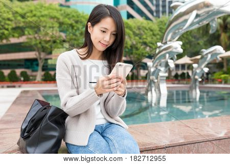 Woman working on cellphone at outdoor