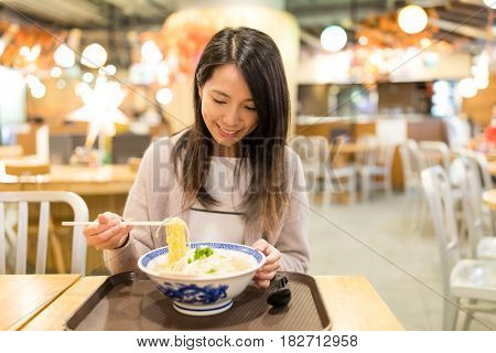 Woman enjoy her japanese noodles in restaurant