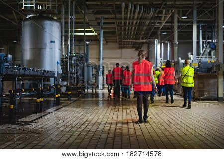 Blonde Woman In Overalls, On The Tour Of The Brewery Plant In Industrial Premises, Amid Crowds Of Pe