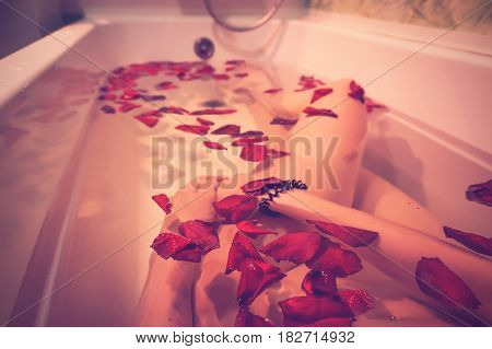 legs of a young girl lying in a white tub with red rose petals. Photo filter instagram