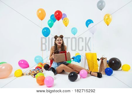 Charming girl after birthday party. Holding huge present box with red bow, sitting on floor