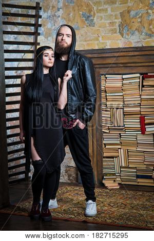 Bearded Man And Girl In A Dress On The Background Of Books.