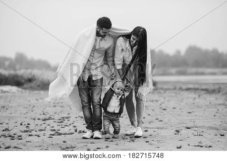 Young family with a little boy to have fun at the beach in autumn