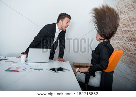 Two angry businesspeople arguing furious showing a negative growth graph at office.