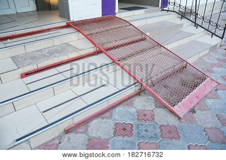 Metal ramp for wheelchair entry and steps.