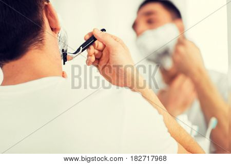 beauty, hygiene, shaving, grooming and people concept - close up of young man looking to mirror and shaving beard with manual razor blade at home bathroom