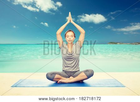 fitness, sport, people and healthy lifestyle concept - woman making yoga meditation in lotus pose on mat over beach background