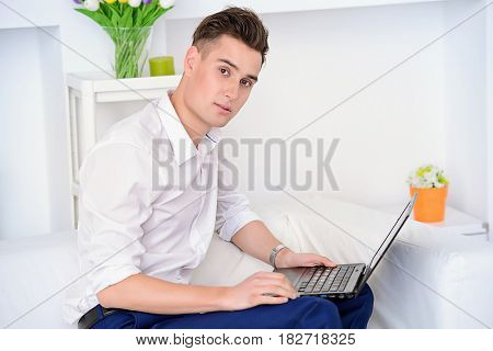 Young man in white shirt working on a laptop. Business concept.