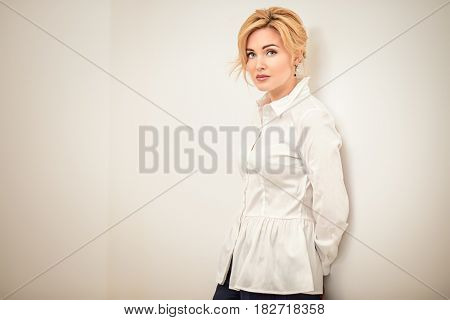 Portrait of a beautiful middle-aged woman in white blouse. Elegant businesswoman in the office.