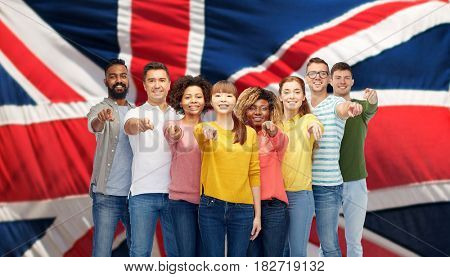 diversity, immigration and people concept - international group of happy smiling men and women pointing finger on you over british flag background