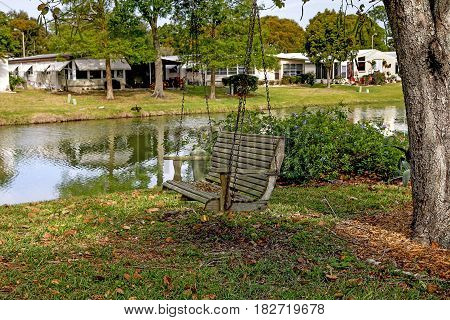 Wooden rocking chair with iron chain in garden tree near a lake in a community of mobile homes