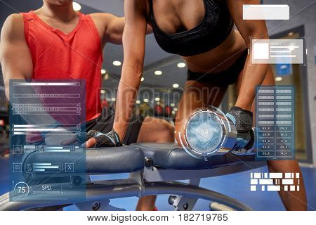 fitness, sport, exercising, bodybuilding and people concept - close up of young woman and personal trainer with dumbbell flexing muscles in gym over virtual charts