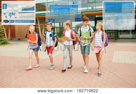 primary education, childhood, communication and people concept - group of happy elementary school students with backpacks walking and talking outdoors over virtual screens with statistics charts
